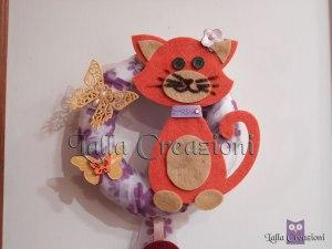 Particolare della decorazione da porta con gatto in feltro e farfalle di carta dorata realizzati con fustelle e big shot
